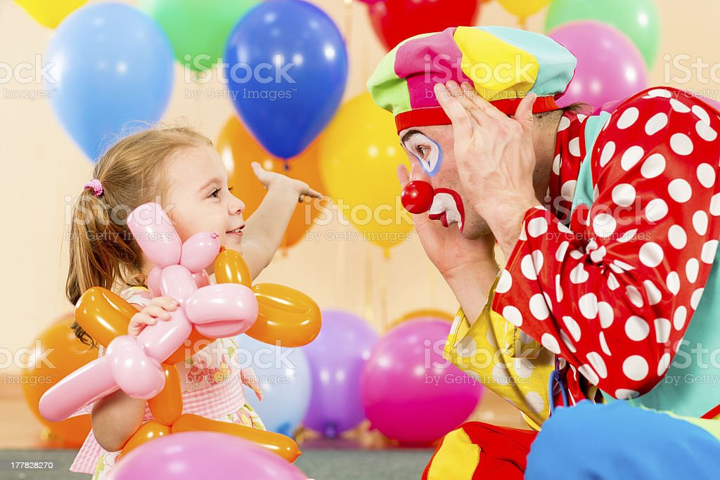 happy child girl and clown playing on birthday party stock photo