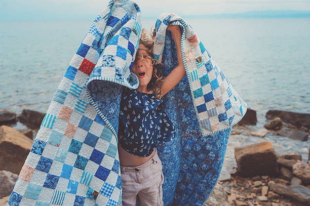 happy child girl covered in blanket at sea, cozy mood - quilt stock photos and pictures