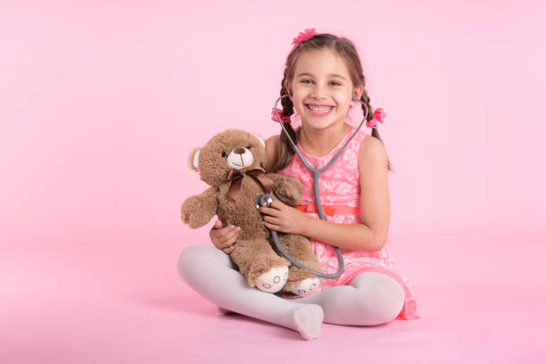 Happy Child Girl Doctor Examining Her Dear Toy Bear on Pink Background stock photo