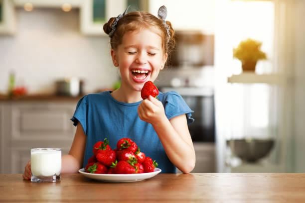 glückliches Kind Mädchen essen Erdbeeren mit Milch – Foto