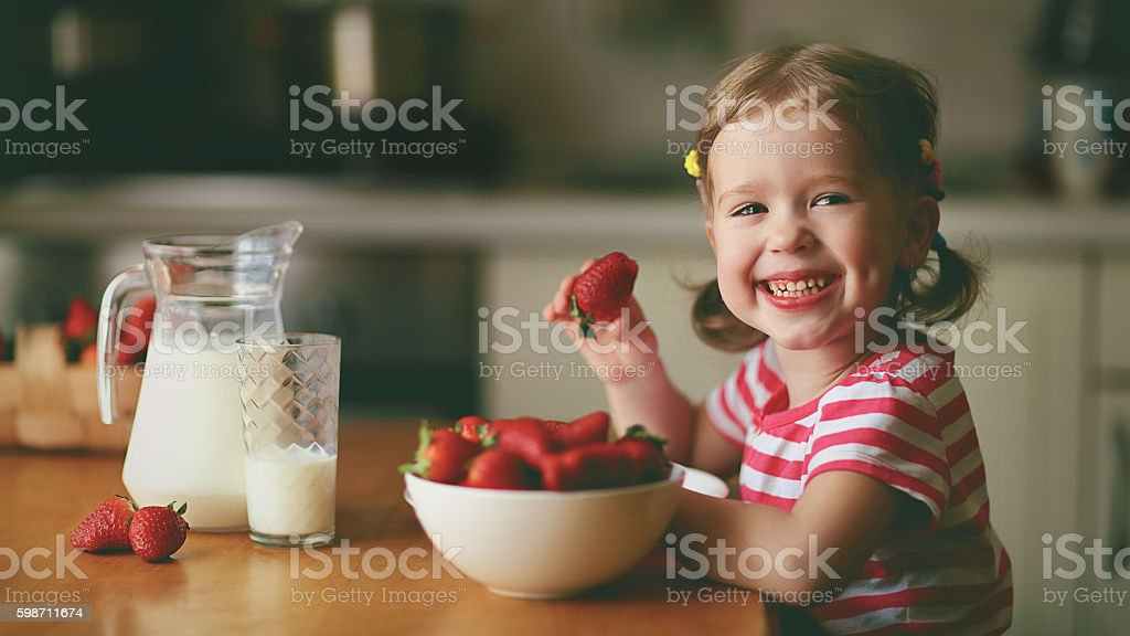 happy child girl eats strawberries in summer home kitchen stock photo