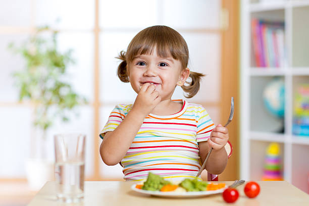 Happy child girl eats vegetables sitting at table in nursery stock photo