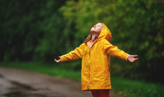 happy child girl enjoying autumn rain
