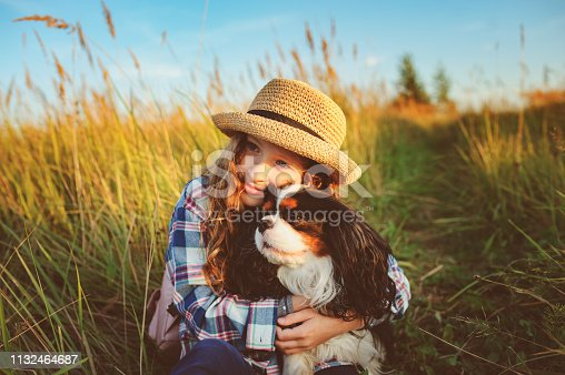 happy child girl enjoying summer vacations with her dog, walking and playing on sunny meadow. Traveling, exploring new places and rural living concept