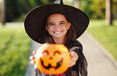 istock happy child girl in a carnival costume and with bucket on Halloween   outdoors 1271018768