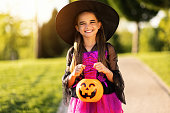 istock happy child girl in a carnival costume and with bucket on Halloween   outdoors 1278454015