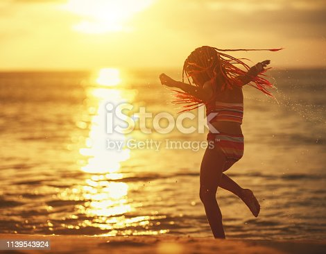 happy child girl in a swimsuit with flying hair dancing on the beach at sunset
