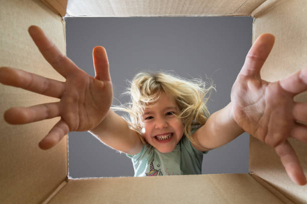 Happy child girl is opening a gift and looking inside cardboard box. stock photo