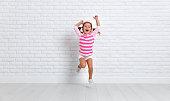 istock happy child girl jumping around empty wall 910874210