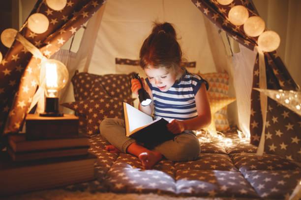 glückliches Kind Mädchen Lachen und Buch in dunkel im Zelt zu Hause – Foto