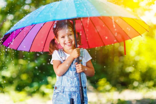 glückliches kind mädchen lacht und spielt im sommerregen mit regenschirm - sonnendusche stock-fotos und bilder