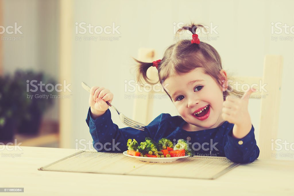 happy child girl loves to eat vegetables stock photo