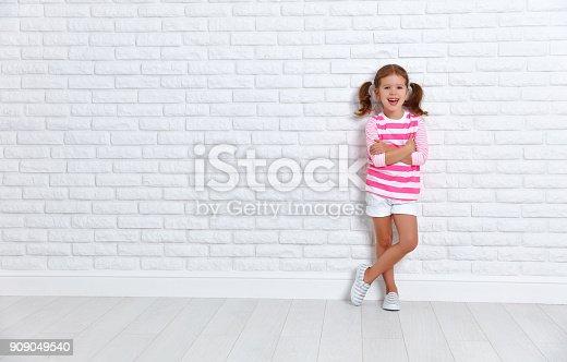 istock happy child girl near an empty brick wall 909049540