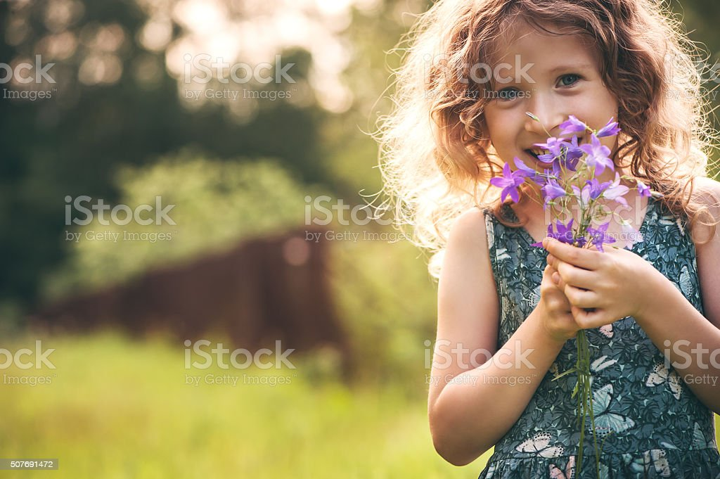 Happy child girl playing with bouquet of bluebells in summer stock photo