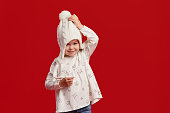 istock Happy child girl pulls a knitted winter hat on her face. isolated on red background 1189342210