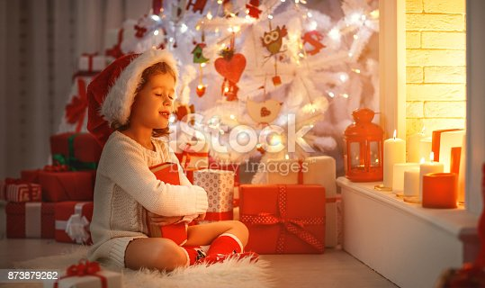 868220646istockphoto happy child girl read book at christmas near   fireplace at home 873879262