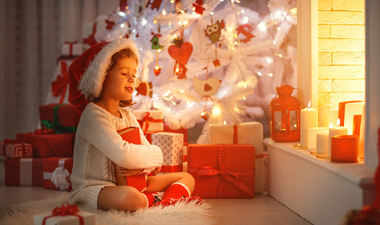 868220646 istock photo happy child girl read book at christmas near   fireplace at home 873879262
