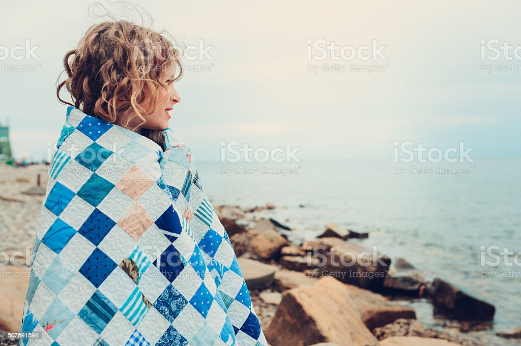 happy child girl relaxing on stone beach, wrapped in blanket stock photo