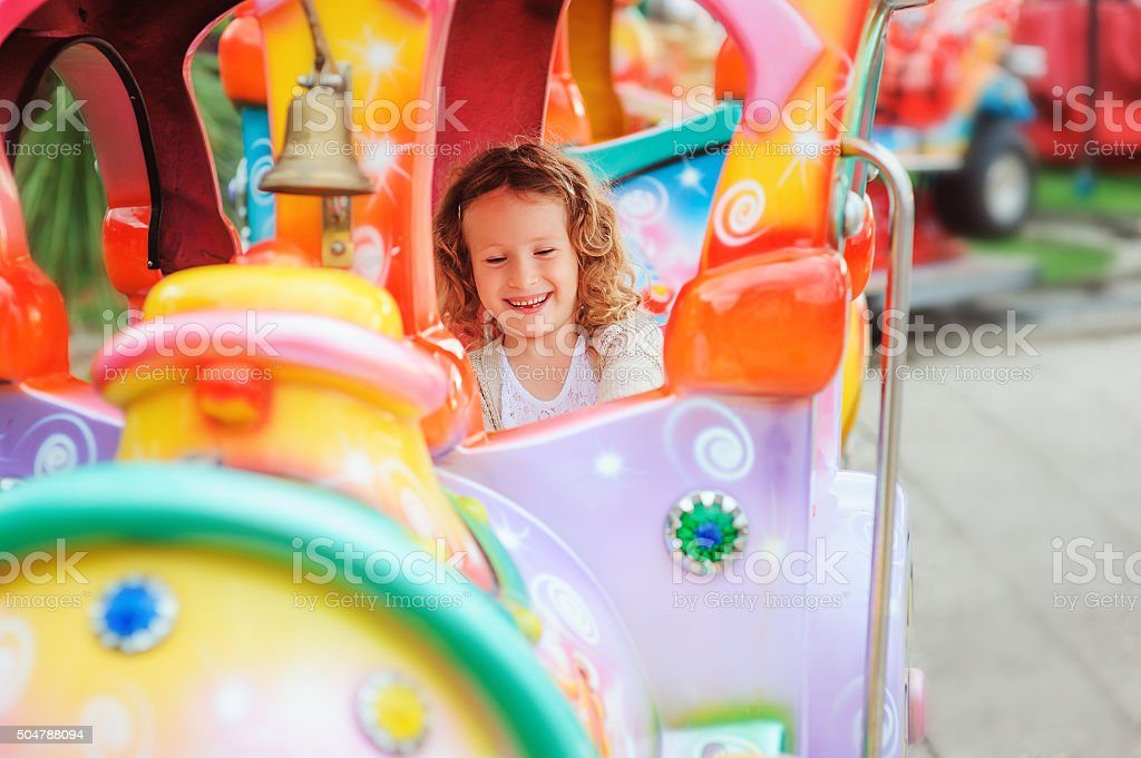 happy child girl riding train on funfair stock photo