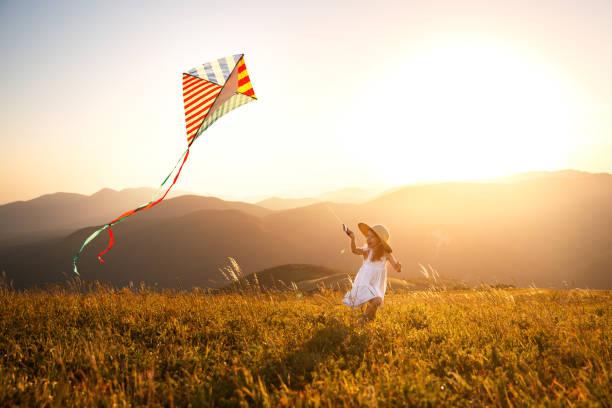 glückliches Kind Mädchen laufen mit Kite bei Sonnenuntergang im freien – Foto