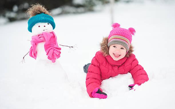 glückliches kind mädchen mit schneemann auf einen winter fuß - schneemann bauen stock-fotos und bilder