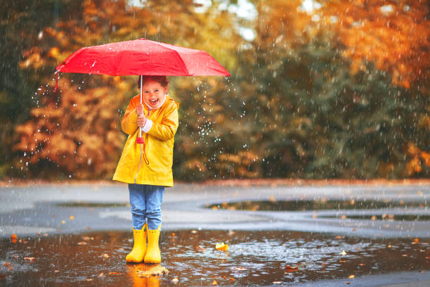 happy child girl with an umbrella and rubber boots in puddle  on autumn walk - umbrellas stock photos and pictures
