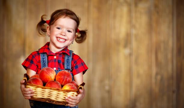 happy child girl with basket of peaches on wooden - pesche bambino foto e immagini stock