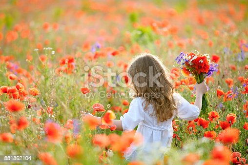 istock happy child girl with field flowers running on meadow in summer in nature 881862104