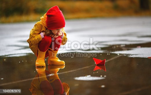istock happy child girl with paper boat in puddle in autumn on nature 1043282970
