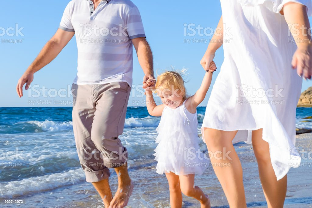 Happy child girl with parents holding hands and having fun walking on the beach. Family vacation, travel concept. Bright sunlight. Copy space. - Royalty-free Adulto Foto de stock
