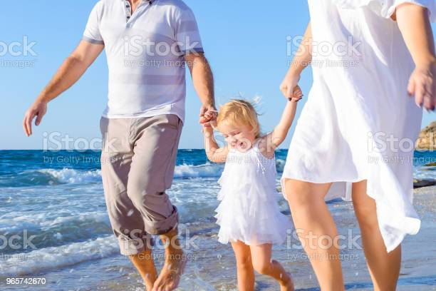 Happy Child Girl With Parents Holding Hands And Having Fun Walking On The Beach Family Vacation Travel Concept Bright Sunlight Copy Space - Fotografias de stock e mais imagens de Adulto