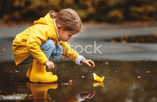 istock happy child girl with umbrella and paper boat in   puddle in   autumn on nature 1010621840