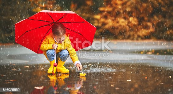 istock happy child girl with umbrella and paper boat in   puddle in   autumn on nature 846025552