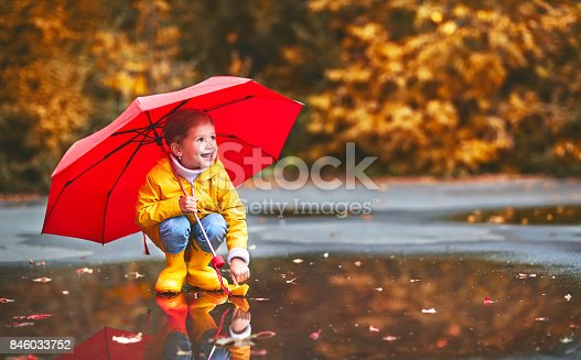 istock happy child girl with umbrella and paper boat in   puddle in   autumn on nature 846033752