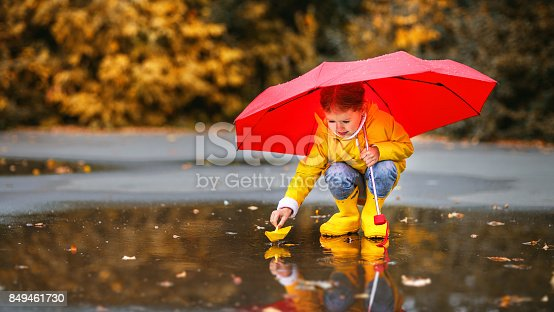istock happy child girl with umbrella and paper boat in   puddle in   autumn on nature 849461730