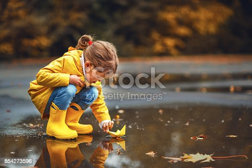 istock happy child girl with umbrella and paper boat in   puddle in   autumn on nature 854273596