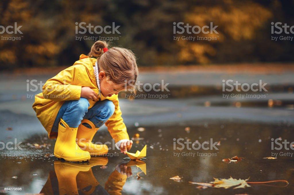 menina criança feliz com guarda-chuva e papel barco na poça no outono na natureza - foto de acervo