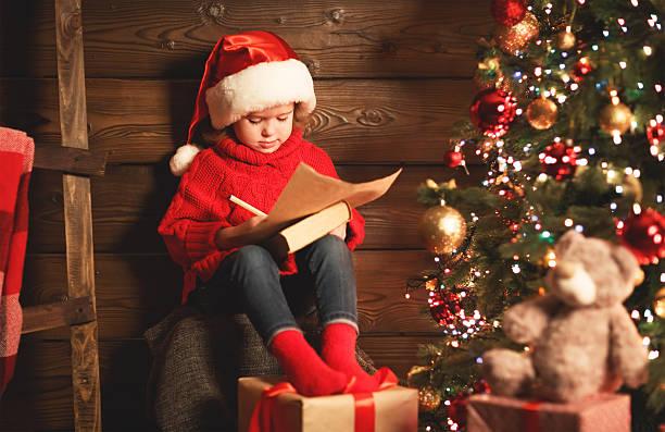 happy child girl writes letter to santa claus at christmas - weihnachts wunschliste stock-fotos und bilder