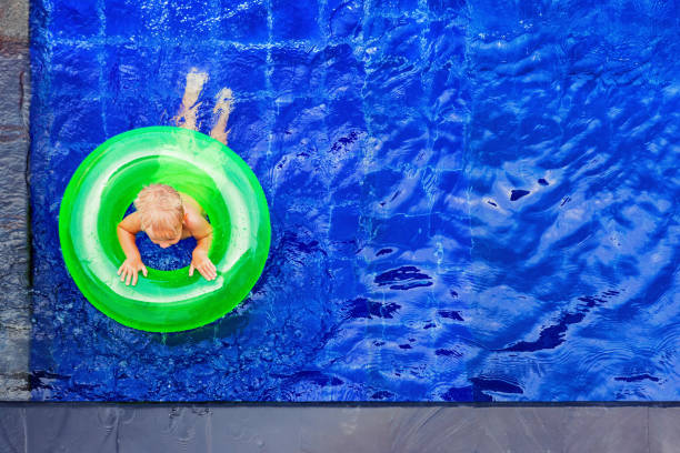 Happy child have fun on inflatable ring in swimming pool stock photo