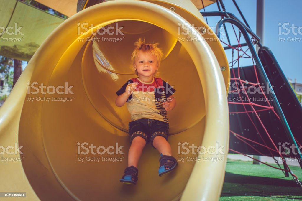 Happy child having fun while sliding at playground stock photo