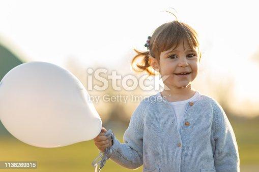 istock Happy child holding balloon 1138269315