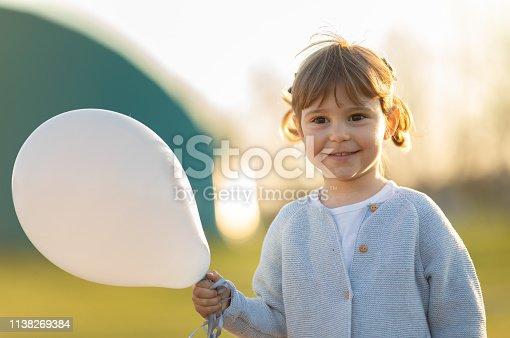 istock Happy child holding balloon 1138269384