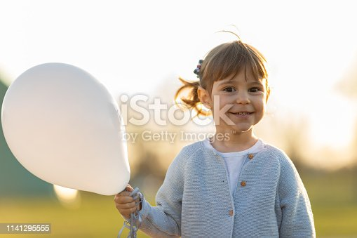 istock Happy child holding balloon 1141295555