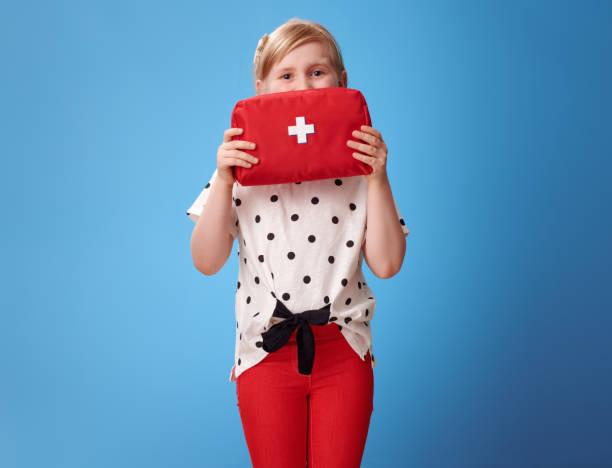 glückliches Kind festhalten Verbandskasten vor Gesicht blau – Foto