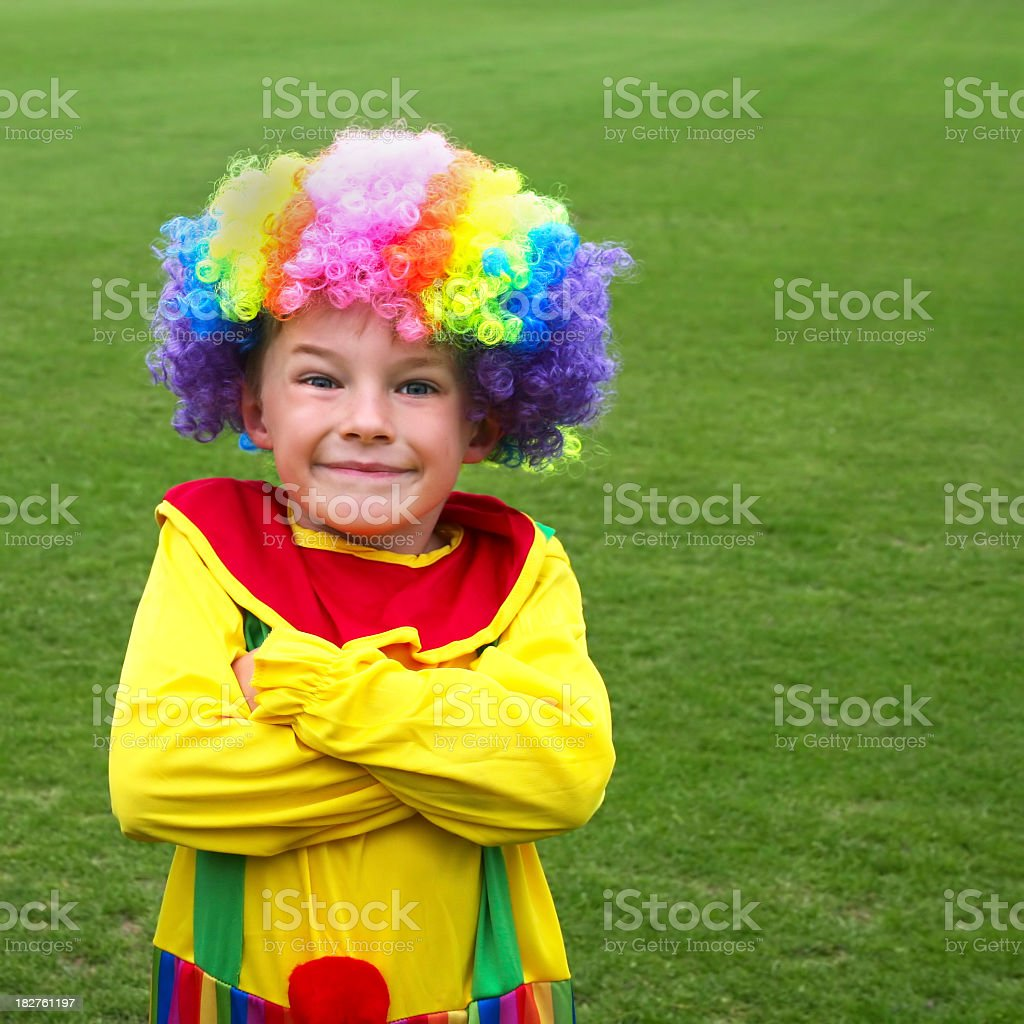 Happy child in brightly coloured clown fancy dress costume royalty-free stock photo