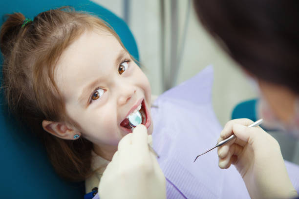 happy child in dentist chair with napkin on chest - dentista foto e immagini stock