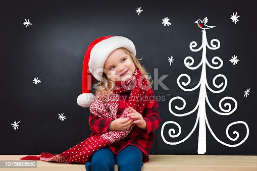 Happy child in Santa red hat with draw Christmas gifts and Christmas tree on blackboard. Christmas holiday concept.