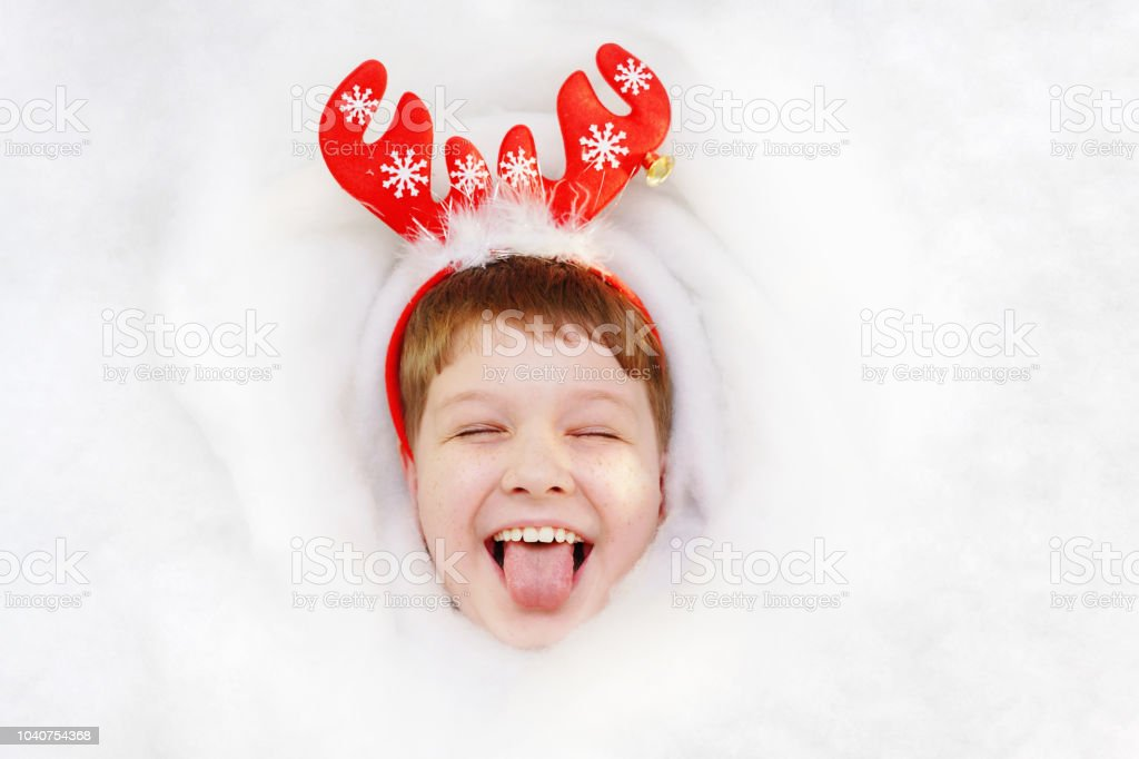 b1da659fd90 Happy Child In Santas Hat Put Out His Tongue Lying In Snow Stock ...