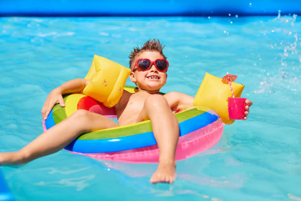 Happy child in sunglasses in the pool with a cocktail. stock photo