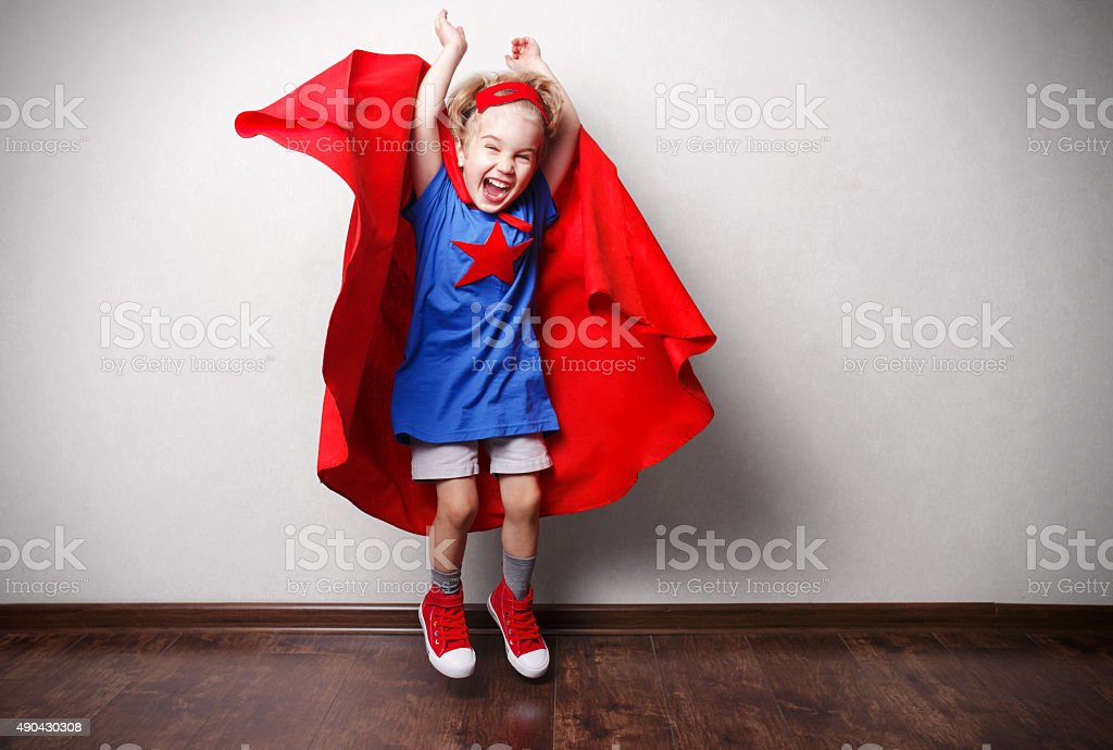 Happy child in superhero suit against gray wall. stock photo